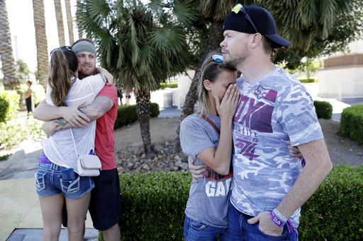 Sean Bean, of Livermore, Calif., hugs his girlfriend Katie Kavetski, of San Leandro, Calif., left, as Travis Reed, of Mexico, Ind., right, comforts his girlfriend Anna Travnicek, second from right, on Las Vegas Strip, Monday, Oct. 2, 2017, in Las Vegas. All attended a concert where a mass shooting occurred on Sunday. (AP Photo/Marcio Jose Sanchez)