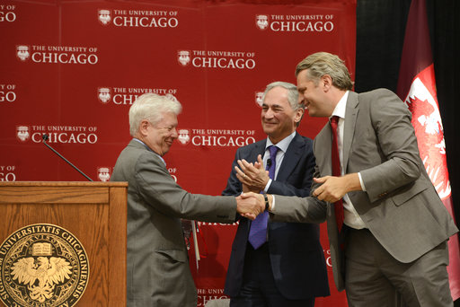 University of Chicago professor Richard Thaler left, shakes hands with University of Chicago provost Dan Diermeir right, while University of Chicago president Robert J. Zimmer, center, looks on during a news conference announcing Thaler as the winner of the Nobel economics prize Monday, Oct. 9, 2017, in Chicago. (AP Photo/Paul Beaty)