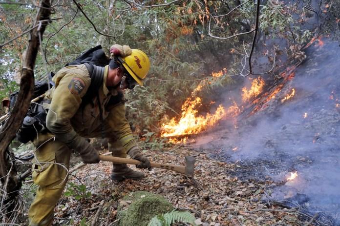 A firefighter builds a containment line as he battles a wildfire Tuesday, Oct. 17, 2017, near Boulder Creek, Calif. (Marcio Jose Sanchez/AP)