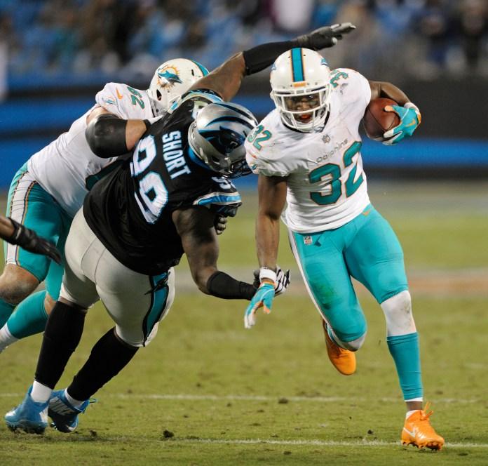 Miami Dolphins' Kenyan Drake (32) runs past Carolina Panthers' Kawann Short (99) in the second half of an NFL football game in Charlotte, N.C., Monday, Nov. 13, 2017. (Mike McCarn/AP)