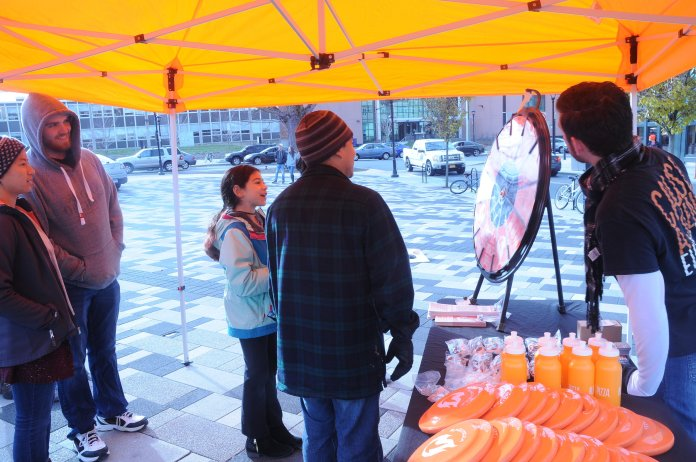 """Children ran around playing in the circle of grass with orange frisbees they had won from spinning the Blaze Pizza """"Wheel of Fire"""" at the annual Winter Welcome event Saturday, Dec. 2 at Storrs Center.(Hanaisha Lewis/The Daily Campus)"""