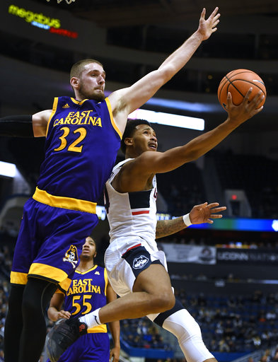 Connecticut's Jalen Adams, right, shoots as East Carolina's Dimitri Spasojevic, left, defends during the second half of an NCAA college basketball game, Saturday, Jan. 6, 2018, in Hartford, Conn. (AP Photo/Jessica Hill)