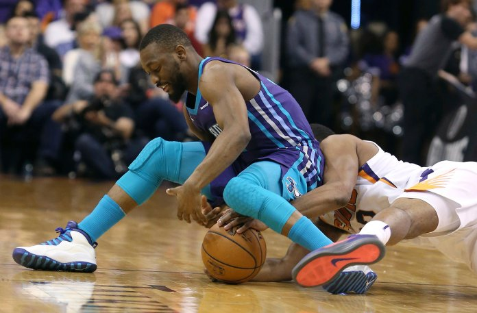 Charlotte Hornets guard Kemba Walker, left, and Phoenix Suns' T.J. Warren battle for the ball during the first half of an NBA basketball game Sunday, Feb. 4, 2018, in Phoenix. (AP Photo/Ralph Freso)