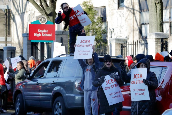 People hold picket signs outside of Henry Snyder High School during a teacher strike, Friday, March 16, 2018, in Jersey City, N.J. The strike began early Friday after the teachers union and the district failed to reach a deal. The two sides have been negotiating since last year, but talks have stalled over health care costs. (AP Photo/Julio Cortez)