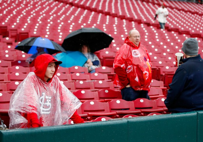 Fans wait out a rain delay before a baseball game between the St. Louis Cardinals and the Cincinnati Reds, Sunday, April 15, 2018, in Cincinnati. (AP Photo/Gary Landers)
