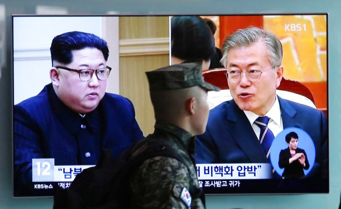 A South Korean marine soldier passes by a TV screen showing file footage of South Korean President Moon Jae-in and North Korean leader Kim Jong Un, left, during a news program at the Seoul Railway Station in Seoul, South Korea, Wednesday, April 18, 2018. North and South Korea have agreed to allow live television broadcasts for parts of the summit between North Korean leader Kim Jong Un and South Korean President Moon Jae-in next week. (AP Photo/Ahn Young-joon)