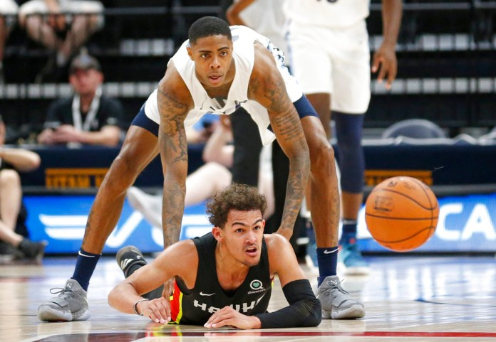Atlanta Hawks guard Trae Young, bottom, and Memphis Grizzlies forward Terry Larrier, top, (28) watch a loose ball during the first half of an NBA summer league basketball game Monday, July 2, 2018, in Salt Lake City. (AP Photo/Rick Bowmer)