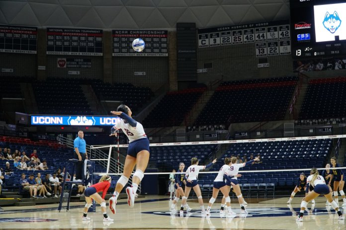 Iman McGary rises for a serve against Quinnipiac on Tuesday, August 28, 2018. (Eric Wang/ The Daily Campus)