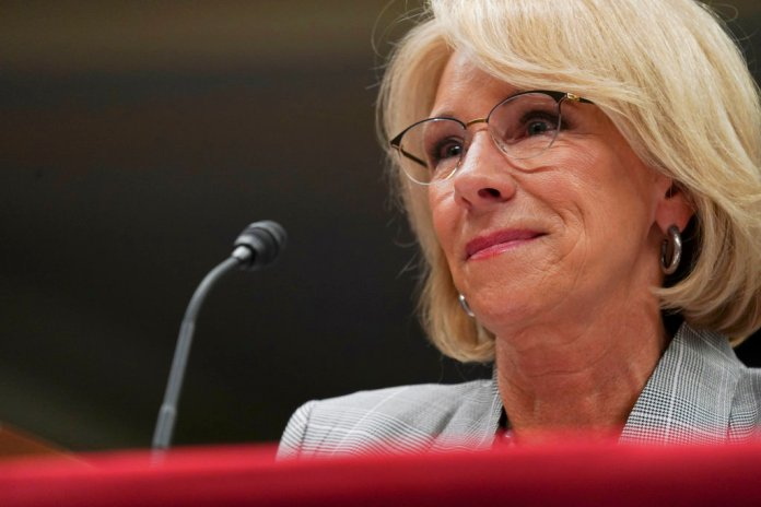 FILE - in this June 5, 2018, file photo, Education Secretary Betsy DeVos pauses as she testifies on Capitol Hill in Washington. Preliminary data obtained by The Associated Press show the Trump administration is granting only partial loan forgiveness to the vast majority of students it approves for help because of fraud by for-profit colleges. The data demonstrate the impact of DeVos' new policy of tiered relief, in which students swindled by for-profit schools are compensated based on their earnings after the program. (AP Photo/Carolyn Kaster, File)