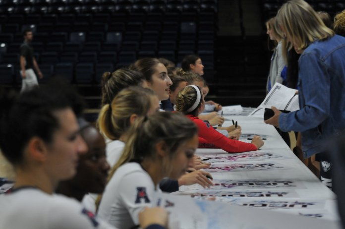The UConn Volleyball team signs team posters during the Dog Pound Challenge. (Hanaisha Lewis, Grab Photographer/ The Daily Campus)