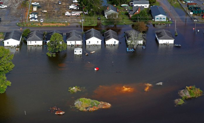 In this Monday, Sept. 17, 2018 file photo, floodwaters from Hurricane Florence surrounds homes in Dillon, S.C. Scientists say climate change likely boosted rainfall totals for both Florence and 2017's Harvey. (AP Photo/Gerald Herbert)