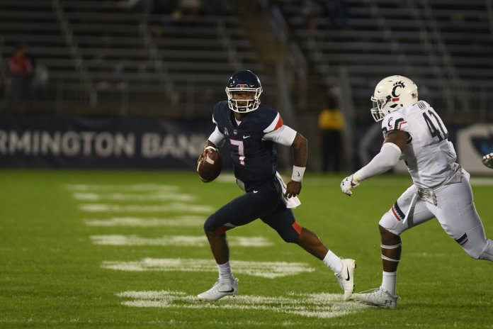 UConn quarterback Marvin Washington scrambles away from a Bearcat defender during a game against Cincinnati on Sept. 29, 2018. (Nicholas Hampton/ The Daily Campus)