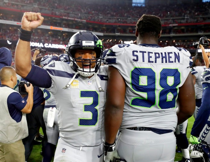 Seattle Seahawks quarterback Russell Wilson (3) celebrates with defensive tackle Shamar Stephen (98) after an NFL football game against the Arizona Cardinals, Sunday, Sept. 30, 2018, in Glendale, Ariz. The Seahawks won 20-17. (AP Photo/Rick Scuteri)