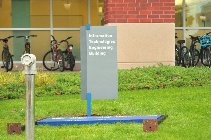 With little explanation, UConn's solid blue and white signage is being replaced in certain places around campus with gray and white signage. A new sign stands triumphantly over its replacement. (Sachin Menon/The Daily Campus)