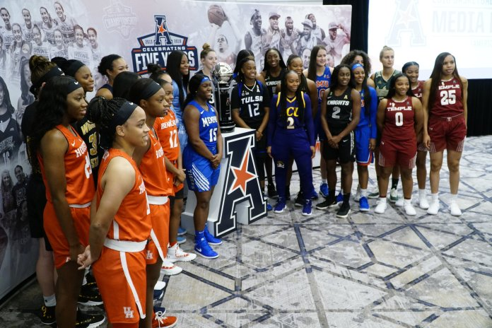Katie Lou Samuelson, Napheesa Collier and Crystal Dangerfield stand with the other players named to the Preseason All-Conference First Team during the American Athletic Conference media day on Monday, Oct. 15. (Eric Wang, Staff Photographer/The Daily Campus)