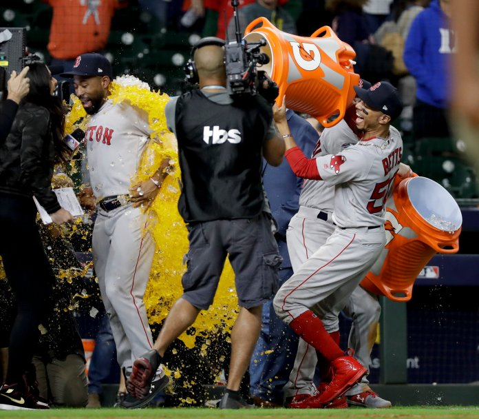 Mookie Betts, pours sports drink on Jackie Bradley Jr. after their 8-2 win over the Houston Astros in American League Championship Series. (AP Photo/David J. Phillip)