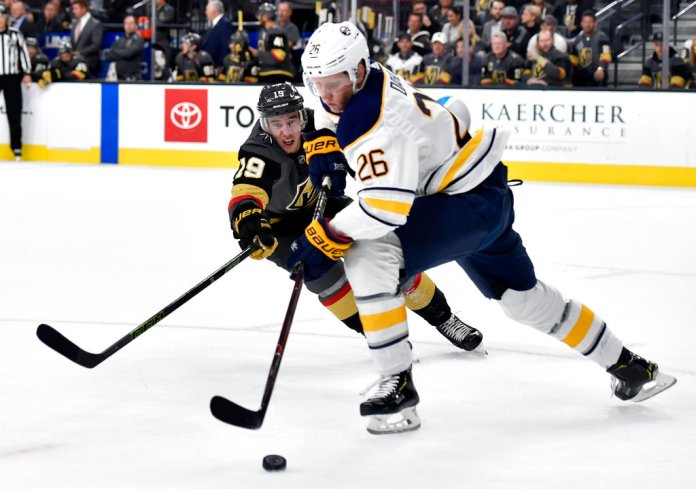 Vegas Golden Knights right wing Reilly Smith (19) and Buffalo Sabres defenseman Rasmus Dahlin (26) skate for the puck during the second period of an NHL hockey game, Tuesday, Oct. 16, 2018, in Las Vegas. (AP Photo/David Becker)