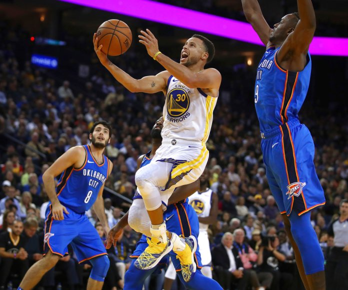 Golden State Warriors' Stephen Curry (30) lays up a shot past Oklahoma City Thunder forward Jerami Grant, right, during the second half of an NBA basketball game, Tuesday, Oct. 16, 2018, in Oakland, Calif. (AP Photo/Ben Margot)