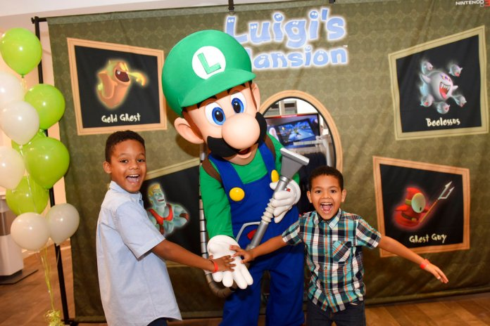 IMAGE DISTRIBUTED FOR NINTENDO OF AMERICA - Joshua A., 9, and Jacob A., 6, of Brooklyn, NY, get into the Halloween spirit during a special event at the Nintendo NY store in Rockefeller Plaza by joining Luigi for a ghost-hunting activity, on Sunday, Oct. 7, 2018, in New York. The spooky classic game Luigi's Mansion will be available for the Nintendo 3DS family of systems on Oct. 12. (Diane Bondareff/AP Images for Nintendo of America)