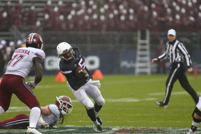 UConn quarterback David Pindell tries to avoid a cluster of UMass defenders. UConn lost 22-17 on Oct. 27, 2018. (Charlotte Lao/ The Daily Campus)