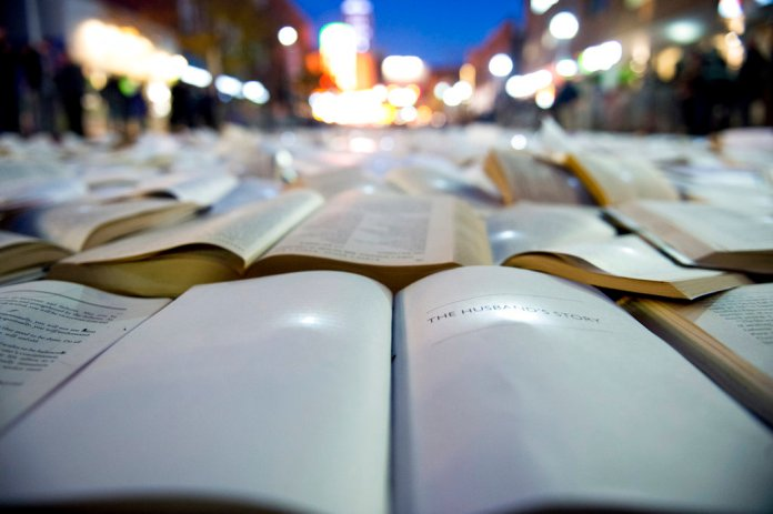 """This Tuesday, Oct. 23, 2018 photo shows thousands of books sit on Liberty Street, as part of a one-night public art installation in Ann Arbor, Mich. The University of Michigan Institute for the Humanities has invited Spain-based art collective Luzinterruptus to work with university and community groups to create the installation titled """"Literature vs. Traffic ."""" The display in Ann Arbor will be on Liberty Street between State and Maynard streets. The event is part of the institute's 2018-19 theme """"Humanities and Environments."""" (Ben Allan Smith /Ann Arbor News via AP)"""