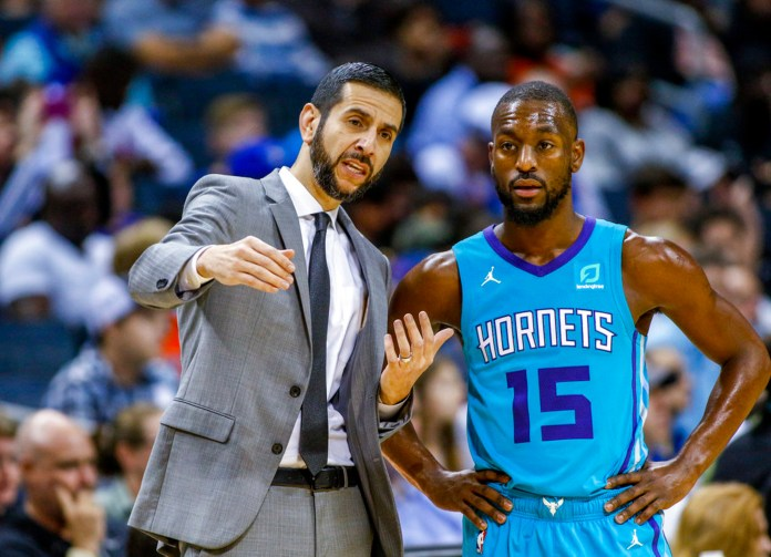 Charlotte Hornets coach James Borrego, left, talks to guard Kemba Walker during a break in the action in the first half of the team's NBA basketball game against the Oklahoma City Thunder in Charlotte, N.C., Thursday, Nov. 1, 2018. (AP Photo/Nell Redmond)