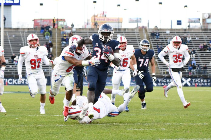 UConn's Kevin Mensah tries to escape a pack of SMU Mustangs on Nov. 10, 2018. (Charlotte Lao/ The Daily Campus)