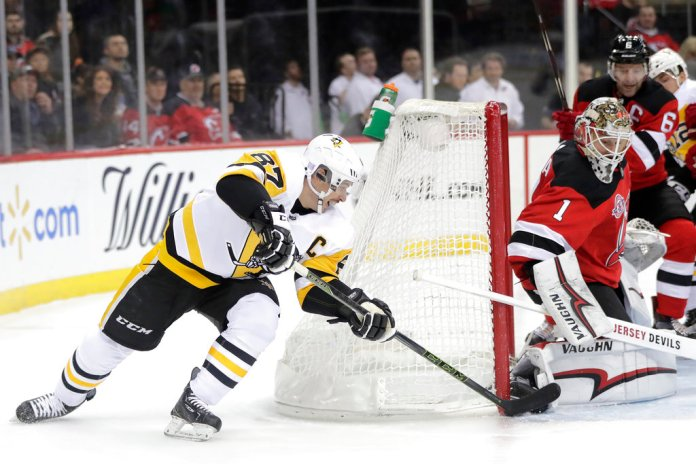 Pittsburgh Penguins center Sidney Crosby (87) attacks on New Jersey Devils goaltender Keith Kinkaid (1) during the first period of an NHL hockey game, Tuesday, Nov. 13, 2018, in Newark, N.J. (AP Photo/Julio Cortez)