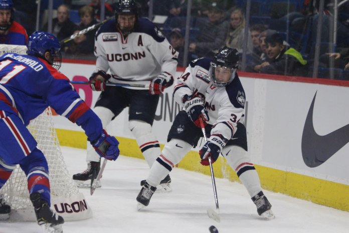 UConn's Ruslan Iskhakov tries to control the puck in his own zone during the Huskies' 5-2 loss to UMass-Lowell on Nov. 16, 2018. (Bryan Lambert/ The Daily Campus)