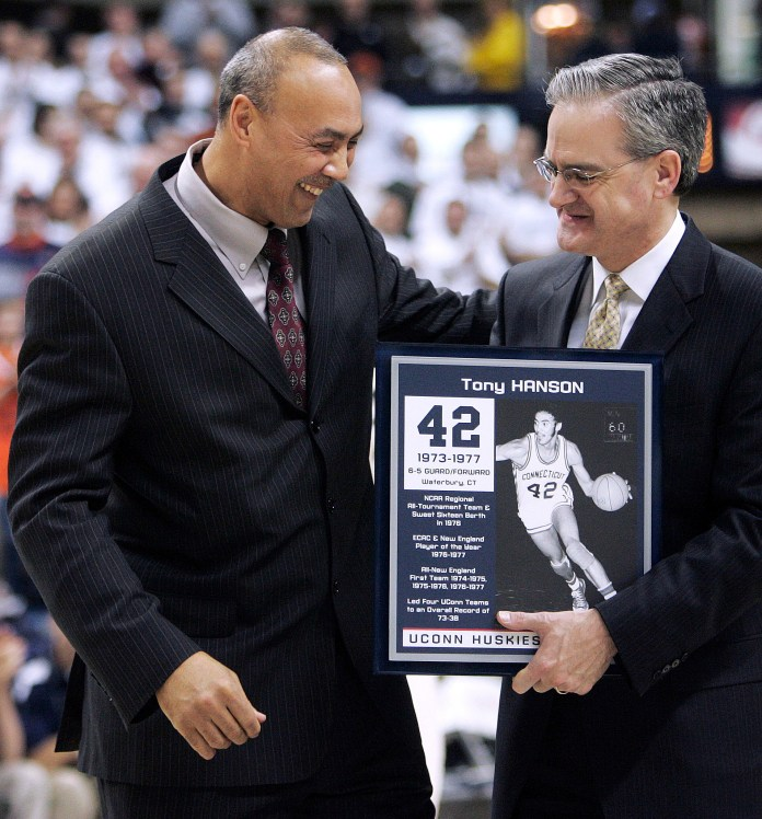Former Connecticut basketball player Tony Hanson, left, shares a light moment with UConn Director of Athletics Jeff Hathaway as Hansen was honored at a basketball game between UConn and Syracuse at Gampel Pavilion on Feb. 5, 2007. (Bob Child, File/AP)