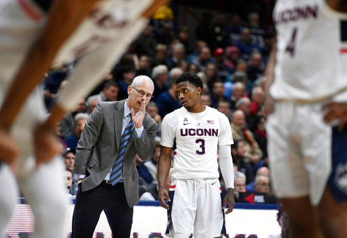 Connecticut head coach Dan Hurley, back left, talks with Alterique Gilbert (3) during the first half of an NCAA college basketball game against SMU, Thursday, Jan. 10, 2019, in Storrs, Conn. (AP Photo/Jessica Hill)
