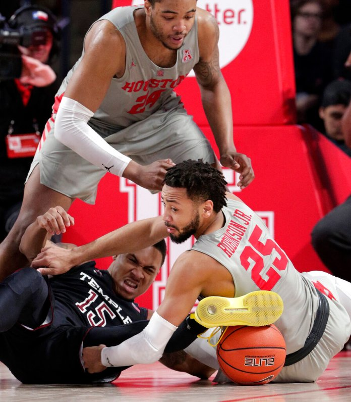 Temple guard Nate Pierre-Louis (15) and Houston guard Galen Robinson Jr. (25) battle for the ball as Houston forward Breaon Brady (24) looks on during the second half of an NCAA college basketball game Thursday, Jan. 31, 2019, in Houston. (AP Photo/Michael Wyke)