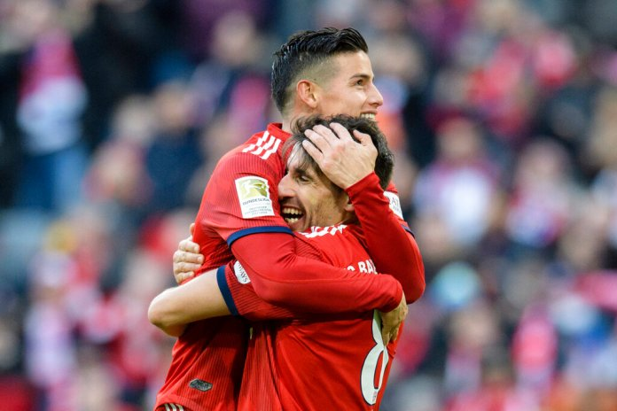 Munich's Javi Martinez, bottom, and James Rodriguez celebrate their side's opening goal during a German Bundesliga soccer match between Bayern Munich and Herha BSC Berlin in Munich, Germany, Saturday, Feb.23, 2019. (Matthias Balk/dpa via AP)