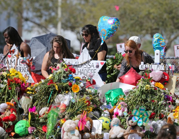 In this Feb. 25, 2018 file photo, mourners bring flowers as they pay tribute at a memorial for the victims of the shooting at Marjory Stoneman Douglas High School, in Parkland, Fla. The community of Parkland, Florida, is focusing on suicide prevention programs after two survivors of the Florida high school massacre there killed themselves this month. Parkland Mayor Christine Hunschofsky said Monday, March 25, 2019, that officials are publicizing the available counseling services after a second Marjory Stoneman Douglas High School student apparently killed himself over the weekend. (David Santiago/Miami Herald via AP, File)