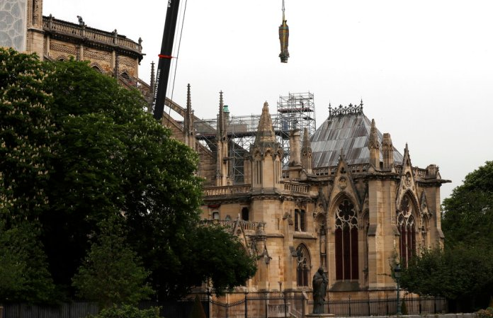 A statue is removed from Notre Dame cathedral,Tuesday, April 23, 2019 in Paris. The man in charge of the restoration of the fire-ravaged Notre Dame cathedral says he has appointed professional mountain climbers to install temporary tarps over the building to offset potential rain damage. (AP Photo/Thibault Camus)
