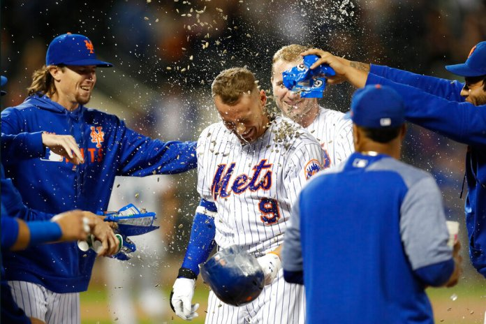 New York Mets' Brandon Nimmo (9) is showered with sunflower seeds after he drew a bases-loaded walk to drive in the winning run against the Miami Marlins in the 11th inning of a baseball game.   Photo by Kathy Willens/AP