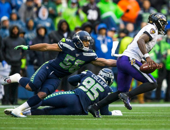 Seattle Seahawks' Mychal Kendricks (56) reaches to try and tackle Baltimore Ravens' Lamar Jackson, right, during an NFL football game Sunday, Oct. 20, 2019, in Seattle, Wash.  Photo by Olivia Vanni/AP