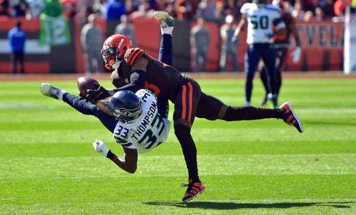 Cleveland Browns wide receiver Odell Beckham Jr. (13) catches a pass under pressure from Seattle Seahawks free safety Tedric Thompson (33) during the first half of an NFL football game.  Photo by David Richard/AP