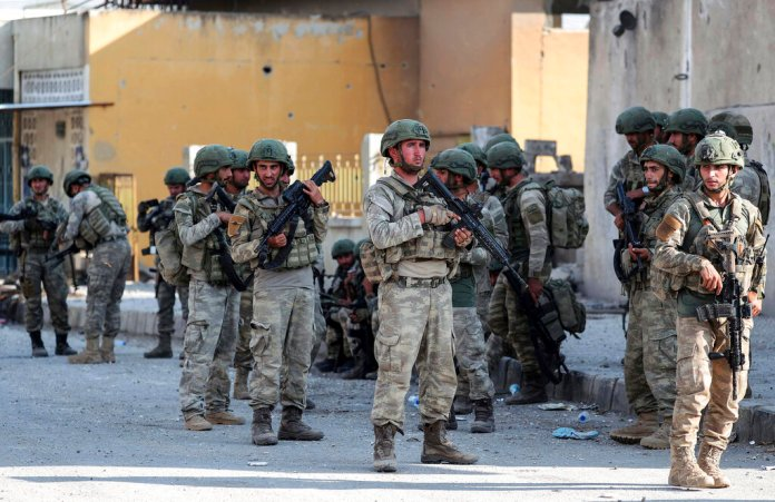 Turkish soldiers secure in Syrian town of Ras al Ayn, northeastern Syria, Wednesday, Oct. 23, 2019. Turkish media reports say Turkish troops and their allied Syrian opposition forces are securing a town in northeast Syria after Syrian Kurdish fighters pulled out of the area.  Photo courtesy of Ugur Can/DHA via AP. Thumbnail photo courtesy of AP Photo.
