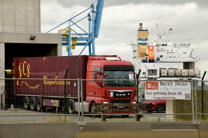 A banner that reads 'Brexit proof' is on a security fence as a truck passes through a scanning tunnel at the Port of Zeebrugge, in Zeebrugge, Belgium, Thursday, Oct. 24, 2019. British police raided two sites in Northern Ireland and questioned a truck driver as they investigate the deaths of 39 people found in a truck container that they believe came from Zeebrugge and was then found at an industrial park in southeastern England.  (AP Photo/Olivier Matthys)