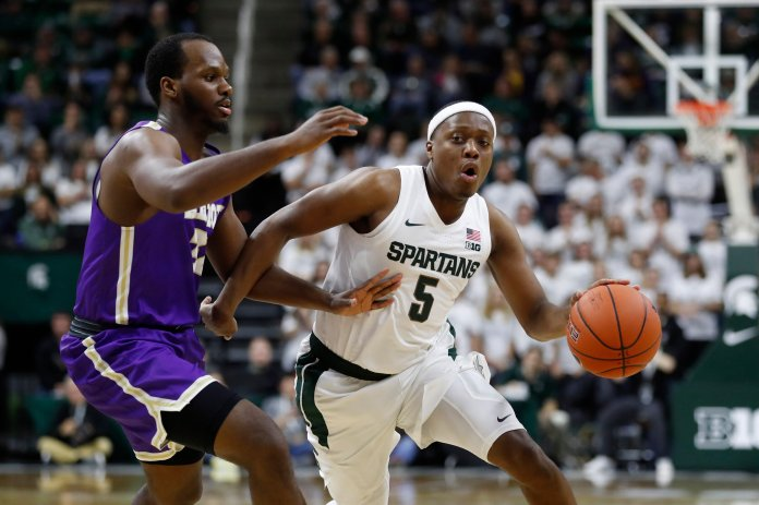 Michigan State guard Cassius Winston (5) drives on Albion forward Quinton Armstrong during the second half of an NCAA college exhibition basketball game, Tuesday, Oct. 29, 2019, in East Lansing, Mich. (AP Photos / Carlos Osorio)