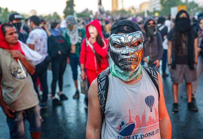 A masked anti-government protester stands with fellow protesters during clashes with police, in Santiago, Chile, Thursday, Oct. 31, 2019.  Photo by Esteban Felix/AP