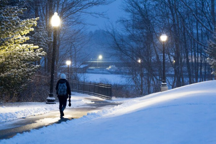 In the coming weeks, as much as you would like to hibernate in your room or in the library, it's important to pay attention to your well-being and take care of yourself during this stressful time before finals. A student walks a snowy path near Hilltop Apartments.  File Photo / The Daily Campus
