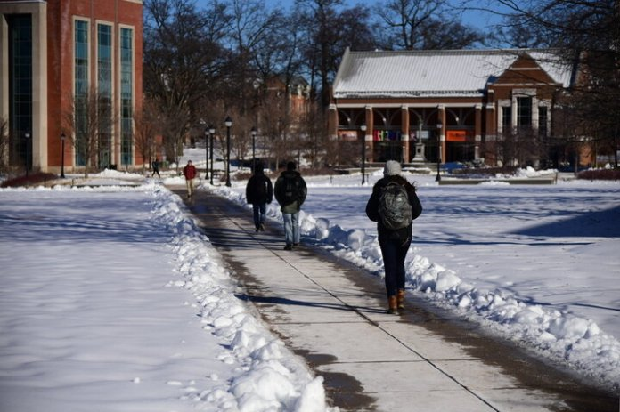 A student strolls through the student union lawn on a snow-covered winter day. Students will be notified of decisions to delay or cancel classes by 5 a.m. The fastest way to be alerted of a decision would be to sign up for text message notifications from the University.  File Photo / The Daily Campus