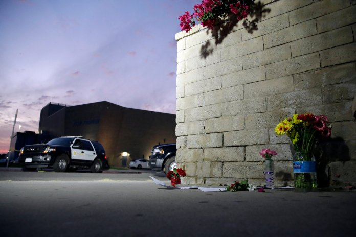 """Flowers are placed in front of Saugus High School in the aftermath of a shooting on Thursday, Nov. 14, 2019, in Santa Clarita, Calif. The """"No Notoriety"""" campaign focuses on the culture of mass shootings and how the media covers them — by virtually erasing all mentions and pictures of the shooter. (AP Photo/Marcio Jose Sanchez)"""