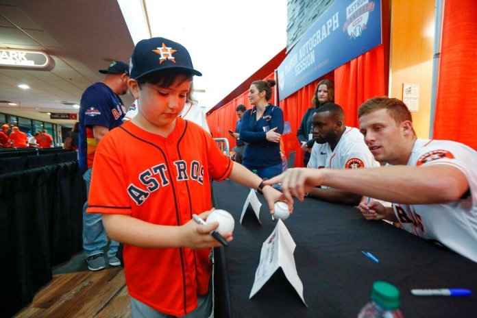 Houston Astros' Myles Straw, right, points to the baseball he signed for Noah Jackson, 9, during FanFest at Minute Maid Park on Saturday, in Houston. It's fans like Jackson that have to answer for the actions of the Astros cheating.  Photo courtesy of Steve Gonzales/Houston Chronicle via AP