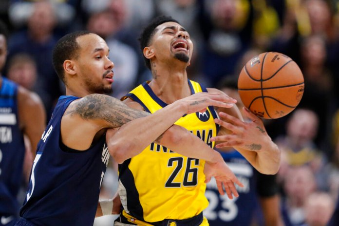 Minnesota Timberwolves guard Shabazz Napier fouls Indiana Pacers guard Jeremy Lamb (26) during the second half of an NBA basketball game in Indianapolis. The Pacers won 116-114.  Photo courtesy of AP Photo/Michael Conroy