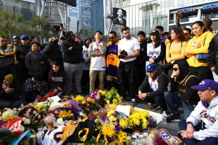 People gather at a memorial for Kobe Bryant near Staples Center Sunday, Jan. 26, 2020, in Los Angeles.    Photo by Michael Owen Baker/AP