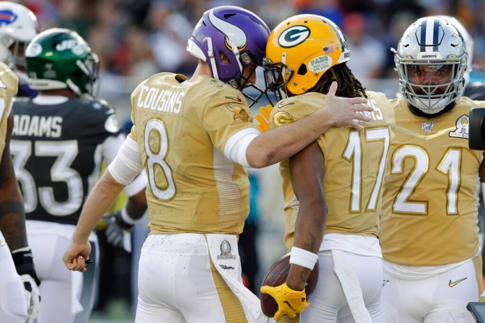 NFC quarterback Kirk Cousins, of the Minnesota Vikings, congratulates NFC wide receiver Davante Adams, of the Green Bay Packers, after Adams scored a touchdown, during the second half of the NFL Pro Bowl football game against the AFC, Sunday in Orlando, Fla. Adams had a special celebration after the touchdown to honor the late Kobe Bryant, who recently died in a helicopter crash.  Photo courtesy of Chris O'Meara/AP Photo
