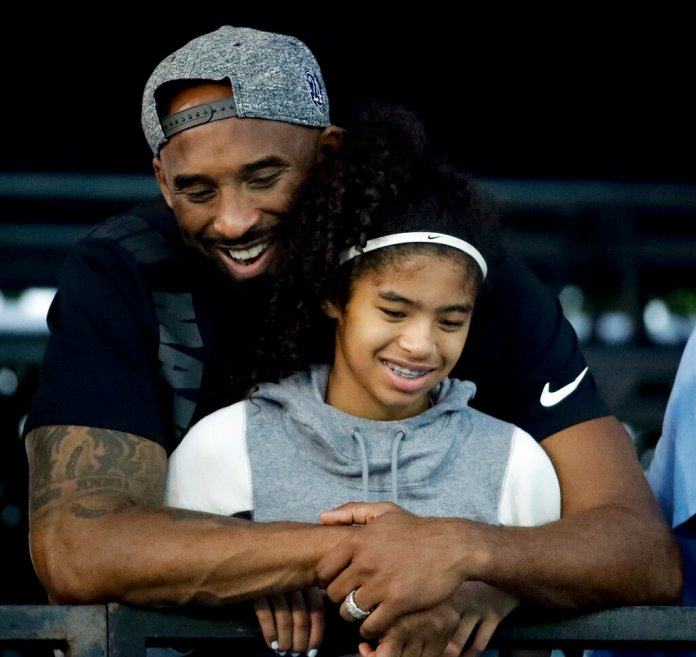 Former Los Angeles Laker Kobe Bryant, 41, and his daughter Gianna, 13, watch during the U.S. national championships swimming meet in Irvine, Calif. Both Kobe and Gianna Bryant died in a helicopter crash Sunday, alongside seven other people. There were no survivors.  Photo courtesy of Chris Carlson/AP Photo